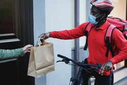 African courier man delivering meal with electric bike - Focus on face