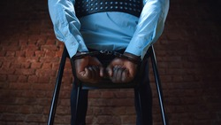 African criminal sitting with hands in handcuffs behind back of chair. Cropped hot of afro-american arrested man sitting handcuffed in interrogation room of police station