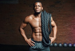 African cross fit coach stands with battle ropes proves that dynamic workout with ropes strengthening athlete s body.