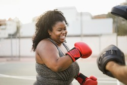 African curvy woman and personal trainer doing boxing workout session outdoor - Focus on face