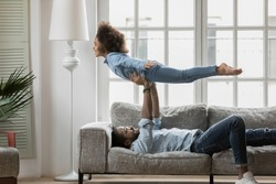 African dad lying on sofa playing with cute little daughter lift up her at stretched arms, happy kid girl imitates plane imagines herself like flying in air, activity at home and family travel concept