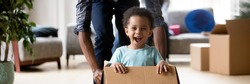 African dad play with excited toddler son riding seated inside of box in moving day at new home, little kid enjoy game with daddy, relocation concept. Horizontal photo banner for website header design