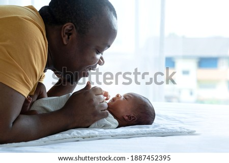 African dad playing tease with newborn baby, newborn baby 15 days old looking his father, African family and newborn concept, father's day