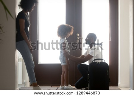 African dad talking to upset mixed race kid daughter leaving family with suitcase in hallway, black father saying goodbye to sad little girl, child of divorced parents and shared custody concept