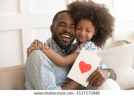 African daddy on Father Day received from caring little daughter paper postcard written message best wishes, drawn red heart as symbol of love and deep affection, family holidays celebration concept