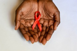 African dark brown skin cupped hands holding red ribbon for HIV AIDS