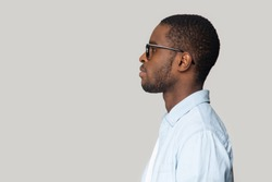 African dark-skinned man in casual blue shirt black framed glasses isolated on gray wall side profile view face, copy space for advertisement text, services promotion, motivated wise thoughts concept