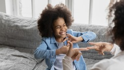 African deaf kid girl and her mother sitting on couch showing symbols with hands using visual-manual gestures enjoy communication at home. Hearing loss disability sign language learning school concept