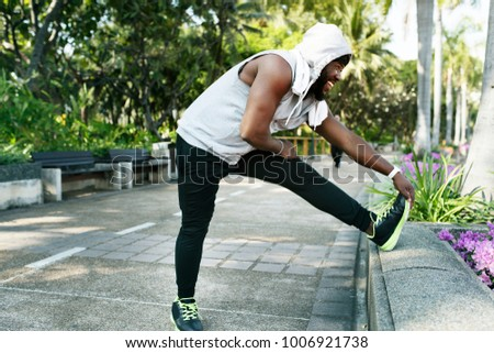 African descent man stretching at the park
