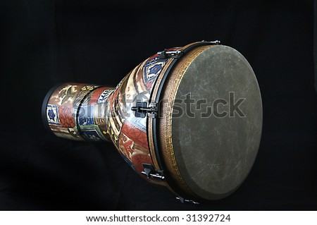 African djembe conga drum isolated closeup on its side against a black background in the horizontal format with copy space.