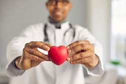 African doctor holding red heart. Selective focus, man's hands in close-up. Concept of good health, cardiovascular diseases prevention, healthy lifestyle promotion, human organ donation, implantation