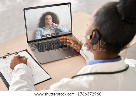African doctor wear headset consult female black patient make online webcam video call on laptop screen. Telemedicine videoconference remote computer app virtual meeting. Over shoulder videocall view.