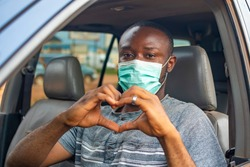 african driver wearing a face mask, doing the heart shape with his hands