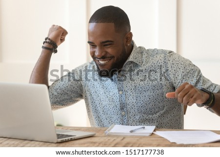 African emotional guy sitting at desk look at notebook screen read message feel excited raise fist makes Yes I did it gesture, students university admission, unemployed got job, lottery winner concept