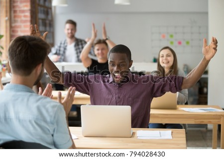 African employee excited about win online raising hands looking at laptop, coworking office team applauding congratulating black colleague with achievement, supporting celebrating success together