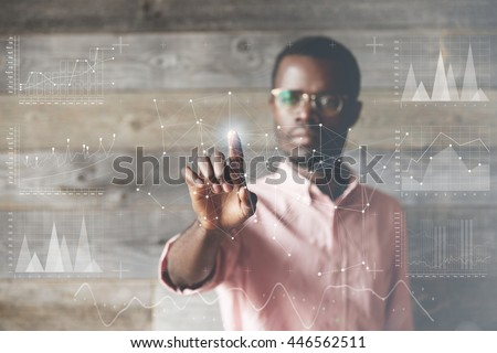African employee, pushing a glowing button at futuristic technology touchscreen display of a main computer to zoom a subject, against wooden interior of his office. Double exposure. Visual effects #446562511