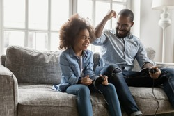 African ethnicity father spend time with little daughter, family sit on couch competing in video games, dad loses excited kid girl win. Weekend activity, free time concept
