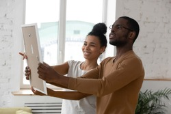 African ethnicity millennial couple holding frame admires painting or photo at relocation day at new first home. Concept of remodeling renovation, new furniture store, bank loan, tenancy rented flat