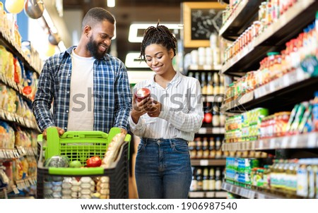 African Family Buying Food In Supermarket Shop Walking Pushing Cart And Choosing Groceries Together. Happy Customers. Black Couple In Grocery Store. Empty Space For Text
