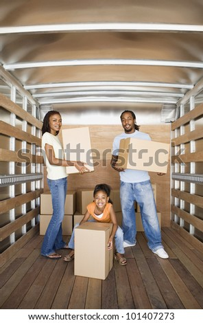 African family holding boxes in moving truck