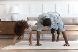 African father and small daughter in casual clothes do pushup pressup exercise on carpet on warm floor in living room, sporty lifestyle, getting physically stronger, have fun, pastime with kid concept