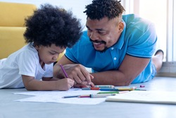 African father and son take the time to draw together while lying on floor in the room, Father's Day, happy time