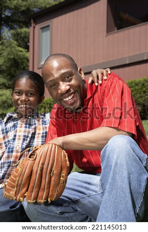 African father and son with baseball glove