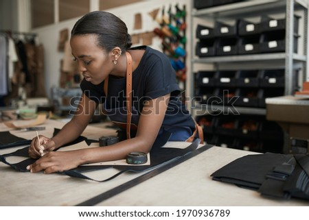 African female artisan using a pattern on leather in her shop Сток-фото ©