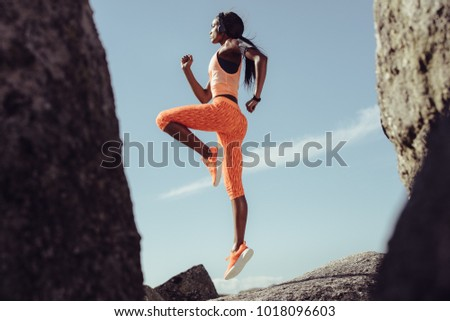 african female athlete jumping...