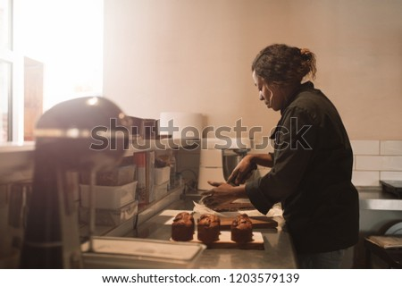 African female baker cutting delicious brownies into portions while working at a counter in a commercial kitchen