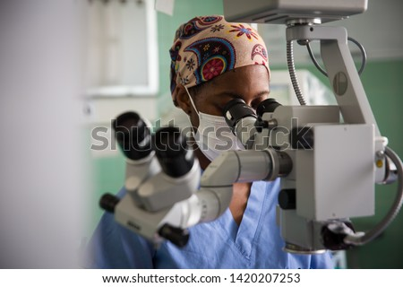 African Female doctor looking through Operating microscope equipment with face mask Cape Town South Africa.