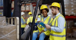 African female fork lift truck driver discussing checklist with foreman in warehouse. Industrial storehouse manager talking with forklift operator discussing shipping plan