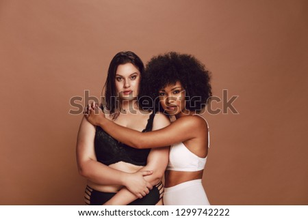 African female hugging oversized woman on brown background. Mixed race females in lingerie staring at camera.