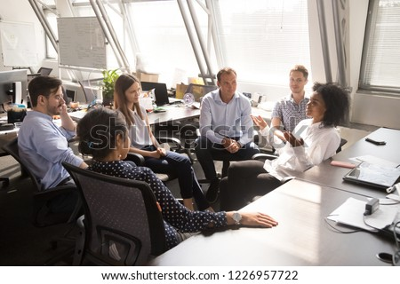African female leader coach mentor teacher speaking to team workers interns explaining new project discussing corporate business plan at multiracial group office meeting or sales corporate training