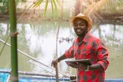 African fish farmer working with using tabket in the  innovation farm.Agriculture or cultivation concept