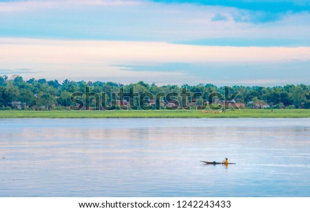 African fisherman rowing boat on Ubangi River, fishing in Bangui capital of Central African Republic. Traditional wooden boat made by African villagers Сток-фото ©