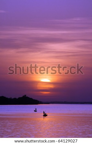 African fishermen on river with sun setting behind them