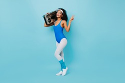 African fitness girls showing peace sign on blue background. Studio shot of shapely female model in aerobics form holding boombox.
