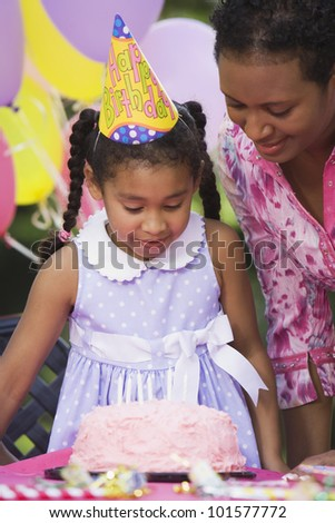 African girl and cake at birthday party
