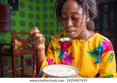 African girl drinking garri and groundnut with milk