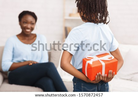 African Girl Hiding Chrismas Gift For Mom Behind Back, Mother Sitting On Couch At Home. Selective focus.