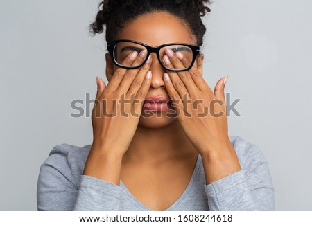 African girl in glasses rubs her eyes, suffering from tired eyes, ocular diseases concept