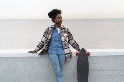 African girl of mix race stand over river view looking aside hold longboard wearing trendy urban style clothes and accessory. Active black woman relax after skateboarding activity outdoors on seaside