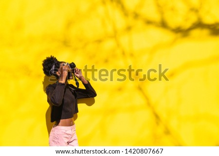 African girl photographer making picture in street