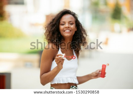 African girl playing with soap bubbles