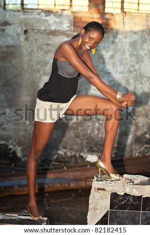 african girl posing on a grungy burned down warehouse