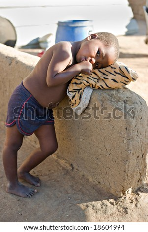 african girl resting in the backyard in a village near Kalahari desert