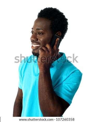 African guy communicating via cellphone and looking away.