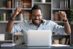African guy feels happy received great news by internet looks at pc screen raised hands scream with joy celebrating on-line lottery win, successful admission to college, offers big discounts concept
