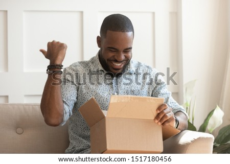 African guy holds on lap carton box looks inside feels excited, man open unpack long-awaited parcel, satisfied online store client, trusted transport company, fragile goods delivered unscathed concept